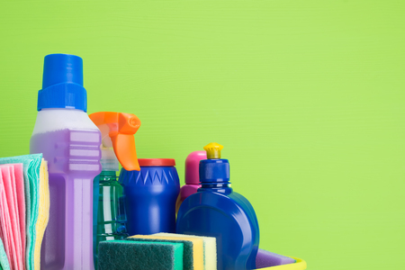 set of liquid and powder products and items for cleaning indoors on a green background, a place for an inscription Stockfoto