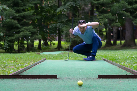 player looks at his hit on a mini golf course Reklamní fotografie