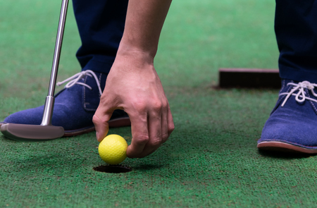 minigolf player pulls a yellow ball out of the hole, close-up Stock Photo