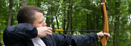 man pulls a bow string for a shot in the forest, close-up, long photo