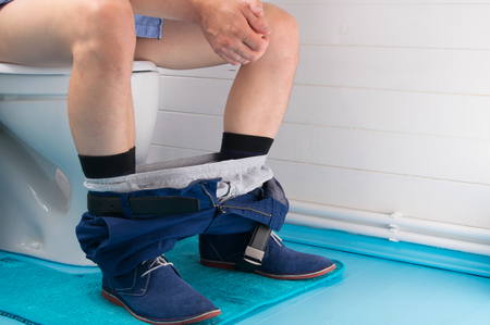 a man in the bathroom, sitting on the toilet, with his pants down Stockfoto