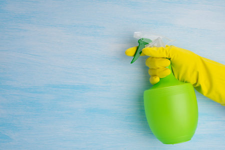 on a blue background, a hand in a yellow glove holds a green bottle for spraying liquids, there is a place for writing on the left