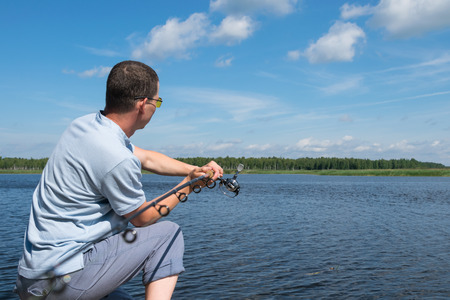 a fisherman on the bank fishes on a spinning on the river against the blue sky Banque d'images