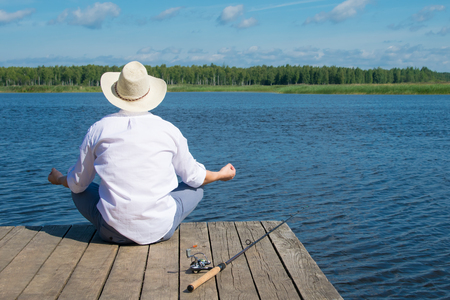 a man meditates on the pier, against the background of water and sky, before fishing 写真素材