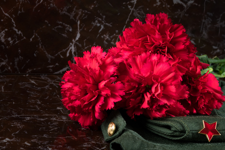 bouquet of red flowers on a military background with a star