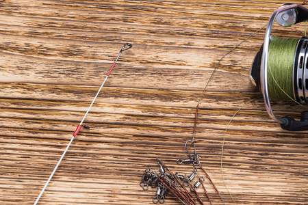 reel with fishing line from fishing pole lies on a wooden burnt background Reklamní fotografie