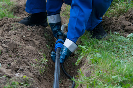 hands of the worker, in blue gloves, laid a plastic pipeline in an open trench in the ground