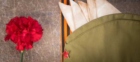 against the background of old paper, red carnation, military cap, St. George ribbon and envelopes