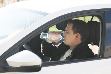 a man driving a white car, drinking cool water from a bottle Imagens