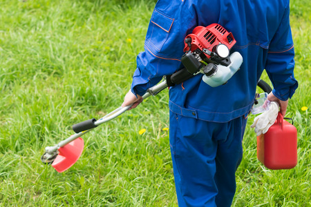 a man in a uniform with a lawn mower is going to cut green grass