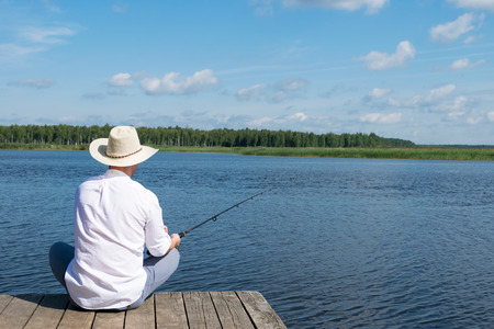 a man in a hat sits on a pier with a fishing rod in his hands and looks at the river