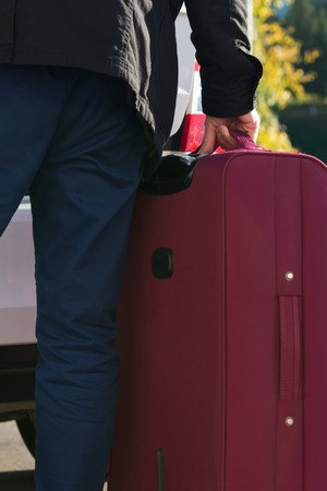 a man is going to put a suitcase with things for rest in the trunk of a car, close-up 版權商用圖片
