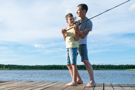 dad teaches son to fish on spinning on the river