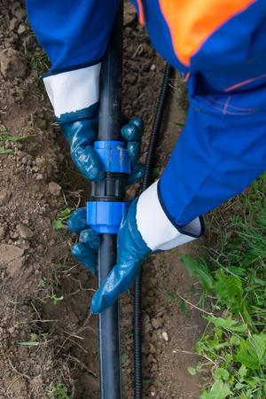 le maître de l'approvisionnement en eau relie la communication en polypropylène dans la tranchée à la maison, en gros plan