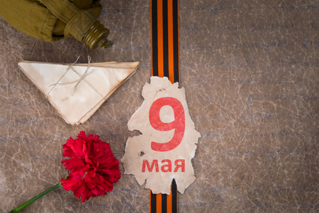 on backdrop of old paper, the old leaf calendar 9 on may, Georgievskaya a ribbon on it, a jar for water, red carnation, letters, right there is place for photo immortal regimen