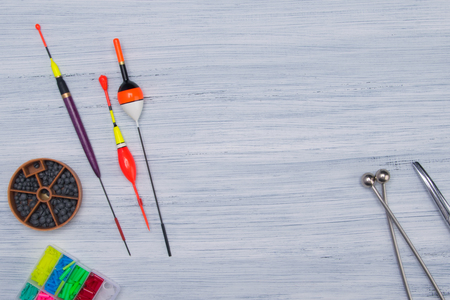 on a gray, wooden table set of items for fishing, sinkers, floats, fishing line, in the center there is a place for advertising Reklamní fotografie