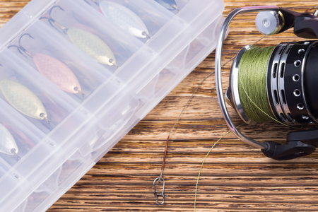 spinning reel and box with different baits on wooden background, close-up