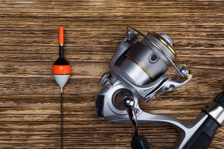 the spinning reel lies on a wooden background next to the float, close-up