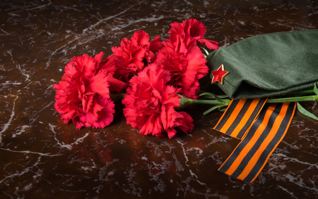 on the background of the monument, a bouquet of red carnations, military cap and St. George ribbon, close-up