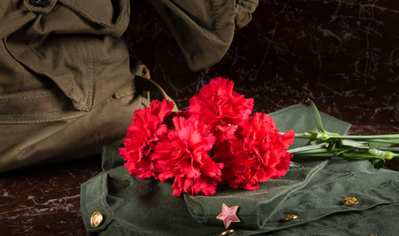 on the background of the monument, a bouquet of red carnations, military uniform, field cap and thing bag