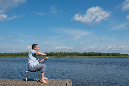 man on vacation is resting on a chair and fishing on the lake