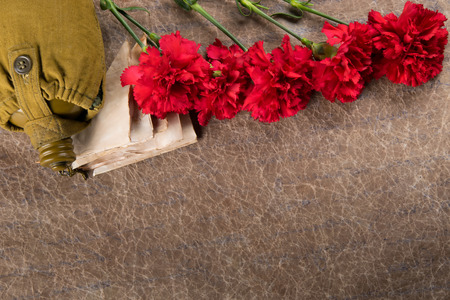 sur fond de vieux papier, un bouquet d'oeillets rouges, des enveloppes et un flacon d'eau, en dessous il y a une place pour une photo