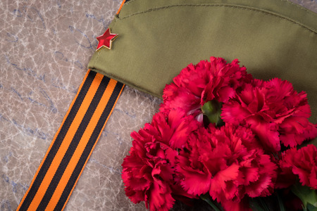 summer hat of a soldier with a red star and St. George ribbon next to a becket of carnations, May 9 holiday, Victory Day