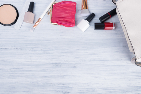 a set of women's accessories, items and cosmetics for applying makeup, which lie next to a white handbag, a place for your inscription Stockfoto