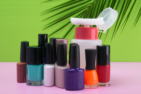 multi-colored nail polishes are on a pink table, on a green background with a palm leaf and a makeup remover with a cotton pad Stock Photo