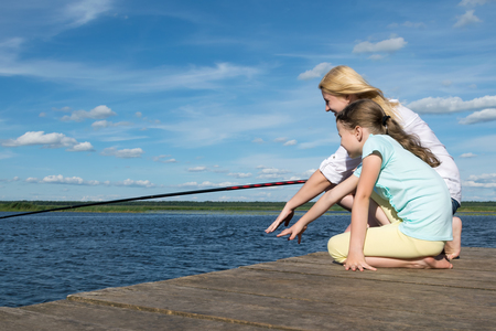 woman with her daughter is fishing on the pier in sunny weather, side view Stockfoto