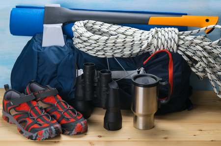 on a wooden table and a blue background, lies a set of traveler, a large blue backpack, binoculars, comfortable shoes rope, thermo mug, hatchet and rolled up, Mat