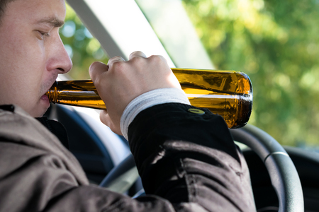 the driver of the car drinks alcoholic beverages behind the wheel