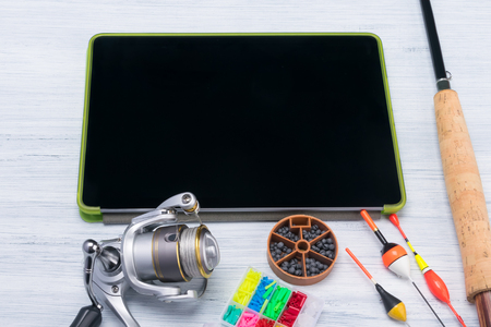 things to collect a fishing pole for fishing lie near the electronic tablet Stock Photo