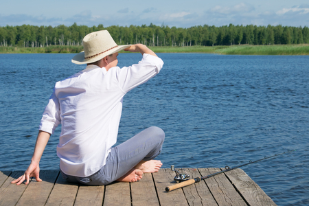 a man in a hat, sitting on the pier and looking into the distance, lying next to the fishing rod for fishing, against the blue sky and the lake