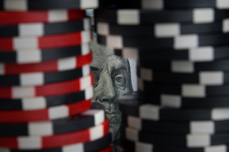 against the background of dollar bills, close-up image, there are two pyramids of game chips