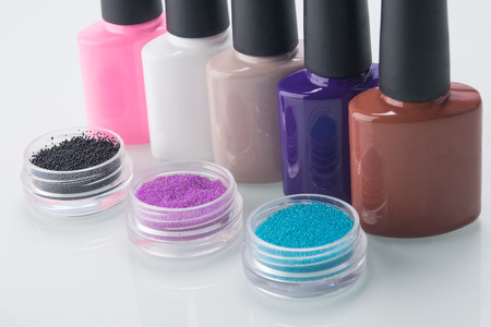 a number of multi-colored varnishes and broths in containers for nail decoration, on a white background, close-up