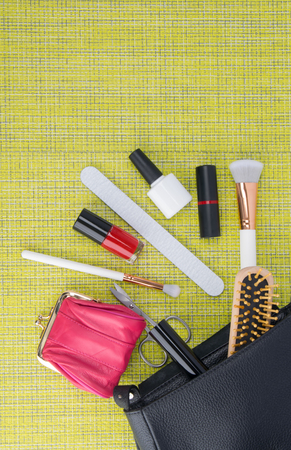 on a green background, lies a black beautician, next to scattered devices for manicure, nail polishes, lipstick, powder brush and pink wallet, with space for an inscription