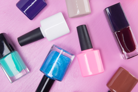 multicolored nail polishes with black caps scattered on a pink background, close-up Stock Photo