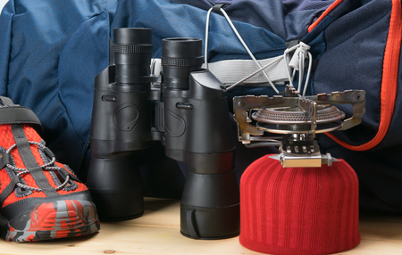 on the wooden table are items for the traveler, a large blue backpack, comfortable shoes, binoculars and a gas burner