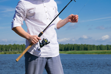 close-up, a mans hand, holds a fishing rod, for catching fish and a hook, against the background of a lake
