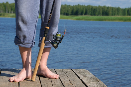 close-up, legs of a man, near spinning for fishing, on a background of blue lake Stock Photo