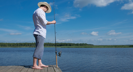 a man in a hat, on the pier, holding spinning, for fishing, against a blue lake and sky Stock Photo