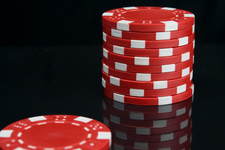 stack of red casino chips on black background with reflection Stock Photo