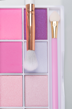 pink, bright eyeshadow set with tassels, close-up, on white background