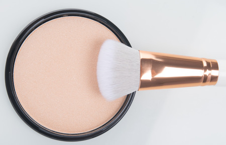 close-up of face powder to smooth the makeup brush on white background