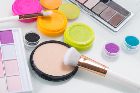 set of makeup tools,powder, shadow, brush and hair decoration with multi-colored powder, on a white table
