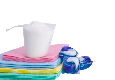 detergent in a measuring glass stands on a multi-colored fabric, capsules with a fabric softener lie next to it, on a white background Stock Photo
