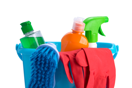 in a blue bucket, multicolored bottles, brush and red rubber gloves, for cleaning surfaces, on a white background Stock Photo