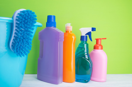 on a light gray and green background, multi-colored bottles with liquids for cleaning surfaces, washing dishes and washing clothes, arranged in a row, next to it is a blue bucket with a brush