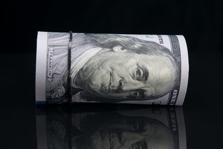 American dollars rolled up, close-up, on a black background with reflection